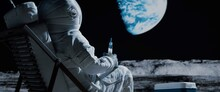 Back View Of Lunar Astronaut Opens A Beer Bottle While Resting In A Beach Chair On Moon Surface, Enjoying View Of Earth