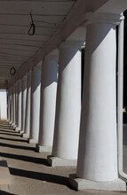 White Columns Cast Shadows On A Sunny Day