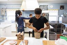 Teenage Boy Volunteer Packing Sack Lunch In Community Center Kitchen