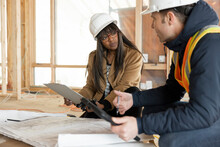 Architect And Homebuilder Discussing Blueprints At Construction Site