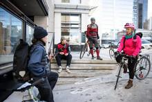 Bike Messengers With Bicycles Taking A Break On City Sidewalk