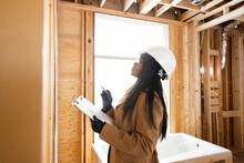 Female Homebuilder Inspecting Framing At Home Construction Site