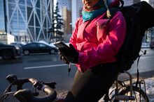 Female Bike Courier With Smart Phone On Bicycle In Winter City