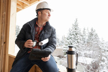 Male Homebuilder With Digital Tablet Drinking Coffee At Winter Site