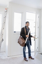 Male Architect Arriving At House Under Construction