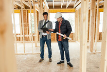 Male Architect And Homebuilder Meeting At Home Construction Site