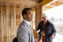 Male Homebuilder And Architect At Construction Site