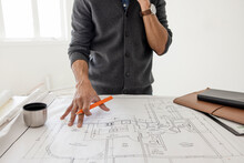 Male Architect Reviewing Blueprints At Construction Site