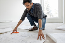 Male Architect Reviewing Blueprints At Home Construction Site