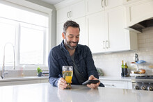 Happy Man Drinking Beer And Using Smart Phone At Kitchen Counter