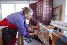Artist Adjusting Print Onto Drying Rack In Art Studio