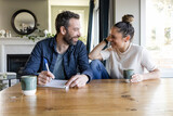 Happy couple enjoying coffee and making a list at dining table