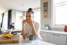 Portrait Happy Woman Eating Orange Slice At Kitchen Counter