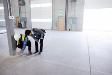 Architect And Contractor Measuring Warehouse Floor