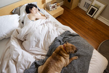 Woman And Dog Sleeping On Bed