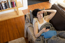 Woman With Cramps Using Hot Water Bottle And Smart Phone On Sofa