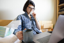 Woman With Allergies Blowing Nose Working From Home At Laptop On Bed