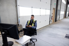 Construction Supervisor Taking Break On Desk In Empty Warehouse