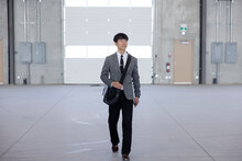 Professional Man Walking Through Empty Warehouse