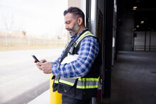 Worker On Phone In Warehouse Doorway