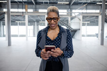 Portrait Of Professional Woman On Phone In Empty Warehouse