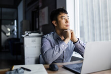 Thoughtful Businessman At Laptop Looking Out Office Window