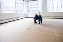 Architect Measuring Empty Office Space