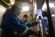 Construction Workers Inspecting Electrical Control Room