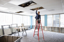 Architect Looking At Wiring In Ceiling Of Empty Office Space