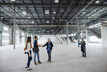 Young Entrepreneurs And Realtor Shaking Hands In Empty Warehouse