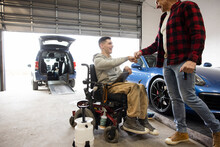 Disabled Male Worker Fist Bumping With Coworker In Auto Body Shop