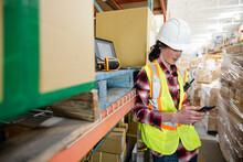 Male Warehouse Worker Using Smart Phone