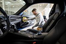 Male Worker Detailing Inside Of Sports Car In Auto Body Shop
