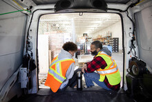Father And Son Warehouse Workers Taking Coffee Break At Back Of Van