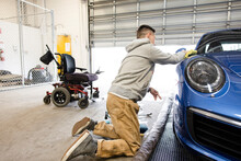 Disabled Male Worker Detailing Blue Sports Car In Auto Body Shop