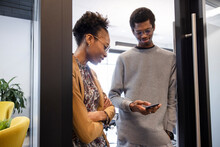Young Business People Using Smart Phone In Office Doorway