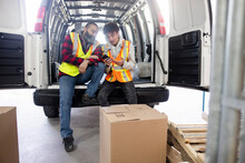 Father And Son Warehouse Workers Using Smart Phone At Van