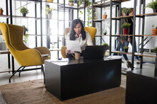 Businesswoman With Paperwork Using Laptop In Modern Office