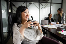 Happy Businesswoman Drinking Coffee In Conference Room Meeting