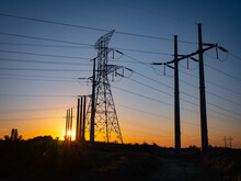Sunset In Silhouettes With Giant Electricity Pylons And Power Cables On The Hills. Glowing Sun Setting Down. Technology Backdrop With Space For Text Or Design