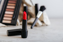 Red Scarlet Lipstick And Set Of Decorative Cosmetics For Make Up On Gray Concrete Background With Copy Space. Minimalistic Beauty Aesthetic.