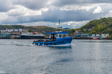 A View Of A Small Fishing Boat Crossing Oban Bay, Oban, Scotland On A Summers Day