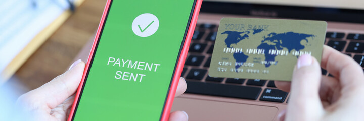 On smartphone screen, inscription payment is sent in hand of bank payment card