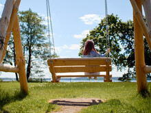 View From Back To Kid With Red Hairs Riding On A Wooden Swing During The Day On The Lawn Against Trees And Blue Sky.