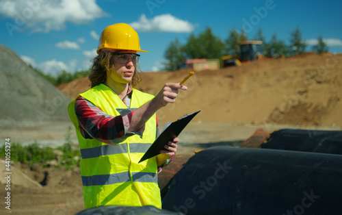 Fotografia, Obraz Building contractor counting number of pipes on the construction site