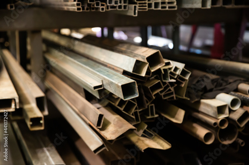 Fototapeta Variety of iron square tubes, round pipes and shaped profiles on rack in metalworking shop