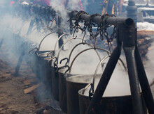 Row Of Iron Cauldrons With Boiling Water For Cooking Over Open Fire During City Holiday Outdoors
