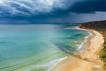 Aerial View Over A Deserted Beach With Dark Storm Clouds Overhead And Rain Falling