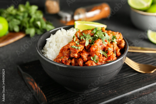 Murais de parede Bowl with tasty chili con carne, rice and lime on dark background, closeup