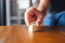 Closeup Image Of A Hand Choosing And Picking A Piece Of Blank Wooden Cube Block